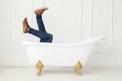 Pés nas calças de brim e nos sapatos de ginástica que olham fora de um banho branco Fotos de Stock Royalty Free
