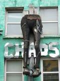 Pés nas calças de brim que penduram abaixo de uma parede Fotografia de Stock