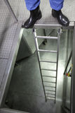 Pés nas galocha na escada do metal Fotografia de Stock Royalty Free