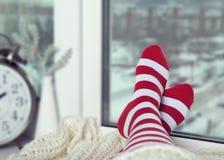 Pés nas peúgas listradas brilhantes contra a janela do inverno Imagem de Stock Royalty Free