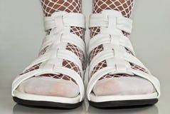 Pés nas sandálias brancas. Imagens de Stock