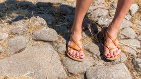 Pés nas sandálias com polimento lascado da unha do pé imagens de stock royalty free