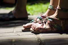 Pés nas sandálias em telhas do fone Fotografia de Stock