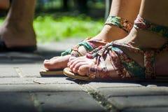 Pés nas sandálias em telhas do fone Imagem de Stock