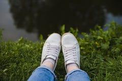 Pés nas sapatilhas brancas na grama pelo rio fotografia de stock