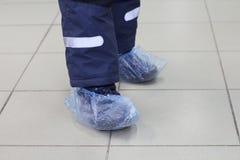 Pés nas tampas azuis da sapata Na foto são dois pés das crianças nas tampas da sapata foto de stock