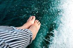 Pés no barco no lago da natureza Imagem de Stock
