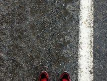 Pés no fundo do asfalto Fotografia de Stock
