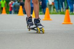 Pés nos patins de rolo que patinam na estrada Fotos de Stock Royalty Free