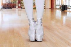 Pés novos da bailarina que estão com pose da ponta do pé fotografia de stock