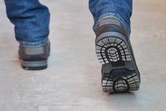 Pés novos do ` s do homem da forma nas calças de brim e botas que andam afastado, única vista Fotos de Stock