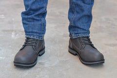 Pés novos do ` s do homem da forma nas calças de brim e nas botas Imagens de Stock Royalty Free