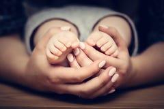 Pés pequenos do bebê no mother& x27; mãos de s A puericultura, sentindo segura, protege Fotos de Stock