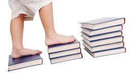 Pés pequenos que pisam em escadas dos livros Foto de Stock