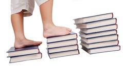 Pés pequenos que pisam nas escadas dos livros isoladas Fotos de Stock Royalty Free