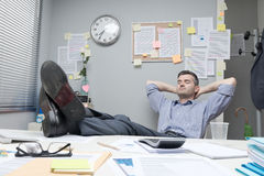 Pés preguiçosos do trabalhador de escritório acima imagem de stock