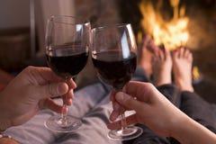 Pés que aquecem-se na chaminé com as mãos que prendem o vinho foto de stock royalty free