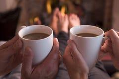Pés que aquecem-se na chaminé com café Fotografia de Stock Royalty Free