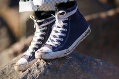 Pés, que estão vestindo as sapatilhas sujas azuis com laços brancos imagem de stock