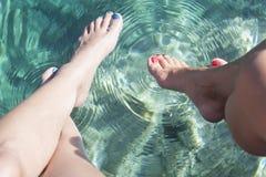 Pés que tocam na água fotografia de stock royalty free