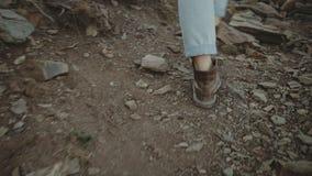 Pés que vestem botas de couro brutais na montanha filme