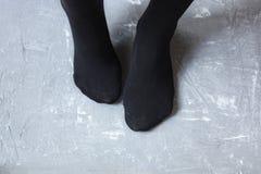 Pés que vestem em peúgas pretas Fotografia de Stock Royalty Free