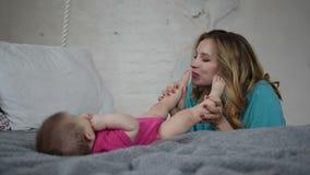 Pés recém-nascidos de beijo do ` s do bebê da mãe bonita filme