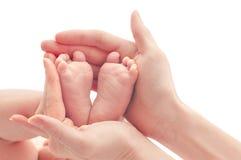 Pés recém-nascidos do bebê nas mãos fêmeas imagens de stock royalty free