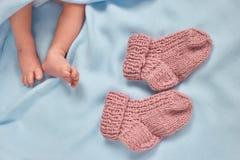 Pés recém-nascidos minúsculos do bebê e peúgas mornas de lãs Fotos de Stock
