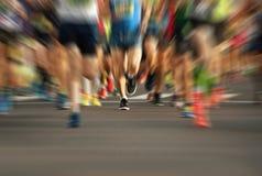 Pés running dos povos da raça da maratona na estrada de cidade Imagem de Stock