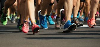 Pés running dos povos da raça da maratona na estrada de cidade foto de stock