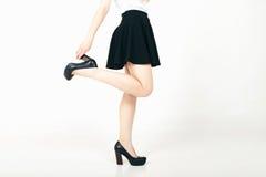 Pés 'sexy' bonitos da mulher com saltos altos pretos e a mini saia Imagens de Stock