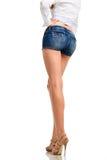 Pés 'sexy' da mulher nos shorts de brim, isolados no fundo branco Imagens de Stock