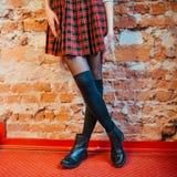 Pés 'sexy' de uma menina na saia e em botas pretas imagens de stock