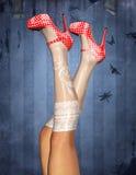 Pés 'sexy' e sapatas vermelhas do às bolinhas Fotos de Stock