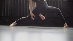 Pés 'sexy' em leggins pretos de movimentos novos da menina do dançarino no movimento lento filme