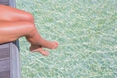 Pés 'sexy' sobre a água do mar clara Fundo tropical da bandeira da praia Fotos de Stock