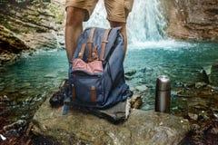 Pés, trouxa e garrafa térmica do homem do caminhante na aventura do fundo da cachoeira que caminha o conceito do curso foto de stock