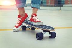 Pés urbanos na moda da mulher no estilo cinemático que levanta no skate Imagem de Stock Royalty Free