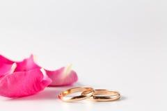 Pétalas de Rosa e alianças de casamento do ouro Fotos de Stock