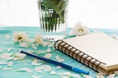 Pétales de carnet et de fleur sur le fond en bois de turquoise, vue de côté de carte d'amour Images libres de droits