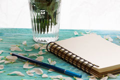 Pétales de carnet et de fleur sur le fond en bois de turquoise, vue de côté de carte d'amour Photos libres de droits