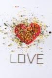 Pétales de fleurs sur le lettrage de coeur et d'amour sur le blanc pour le jour du ` s de valentine Photos stock
