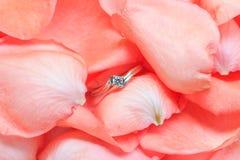 Pétales de rose et anneau de mariage Images stock