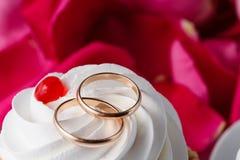 Pétales de rose et anneaux de mariage Photographie stock