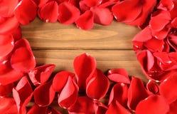 Pétales de rose rouges mous sur le fond en bois Photo stock