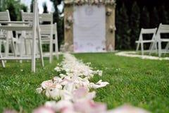 Pétales de rose sur l'herbe, devant le beau treillis de mariage Photographie stock libre de droits