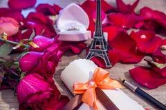 Pétales de roses, argent, bouteilles de vin, une boîte de bijoux et Tour Eiffel Photos stock