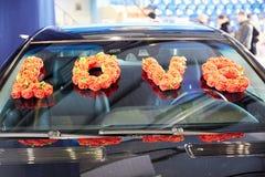 Pétales des roses et des fleurs sur une limousine d'un mariage Images stock