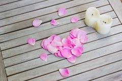 Pétales des roses roses dans une forme de coeur et une bougie Photographie stock libre de droits